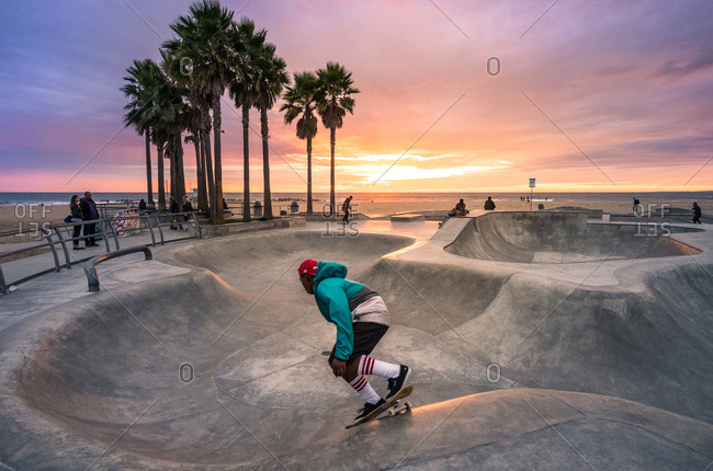 LOS ANGELES, USA - December 17, 2014: Skaters doing tricks in a skate park at sunset in Venice Beach