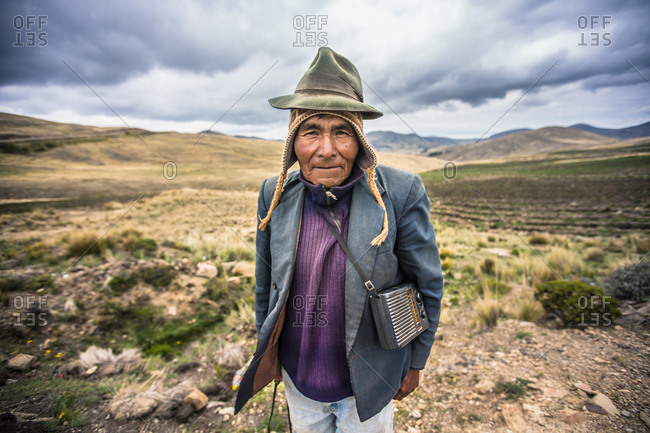 BOLIVIA - December 13, 2013: Old indigenous habitat in warm clothing posing on background of plain and mountains