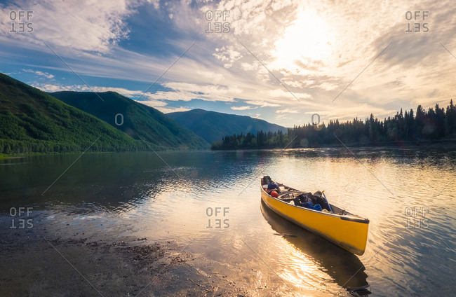 Yellow kayak full of trekking equipment floating on water with mountains on background