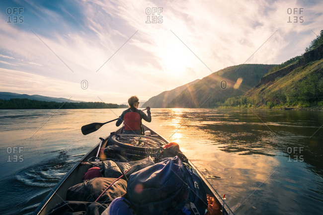 Back view of person rowing in boat full of trekking equipment on background of lake and mountains