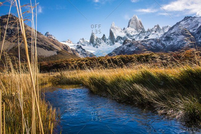 Picturesque view of water flowing on terrain with view of mountains peaks in snow