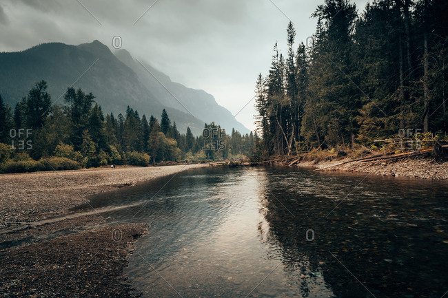 Landscape of mountains and woods in mist and stream of water flowing calmly