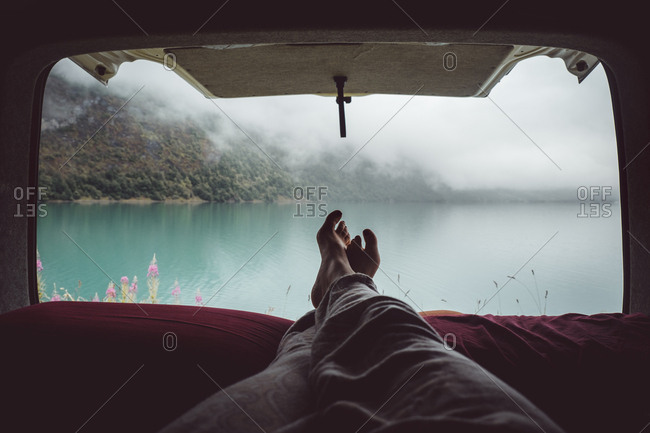Crop legs in van on background of lake and mountains in mist