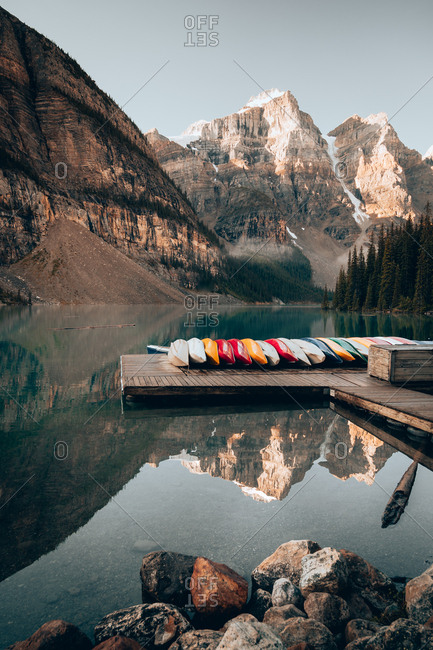 Row of colorful boats lying on wooden pier in lake Moraine on background of mountains and cliffs