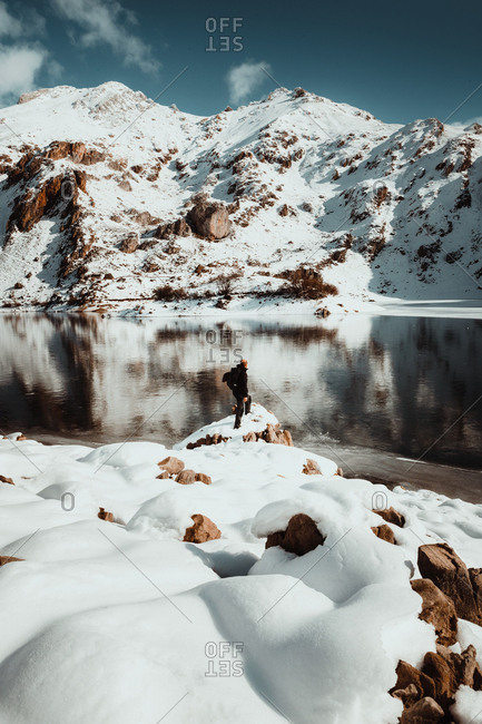 Anonymous traveler posing on rocks covered with snow on background of lake in snowy mountains