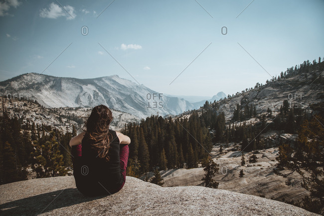 Back view of woman sitting on rock looking at picturesque valley in mountains with coniferous woods