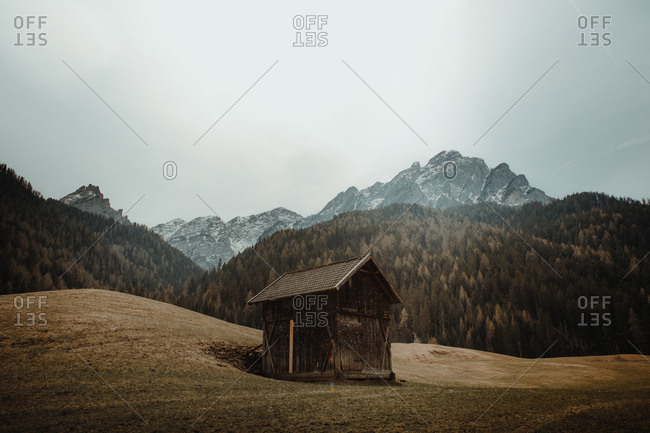 Abandoned house placed on playing below mountains and woods in mist