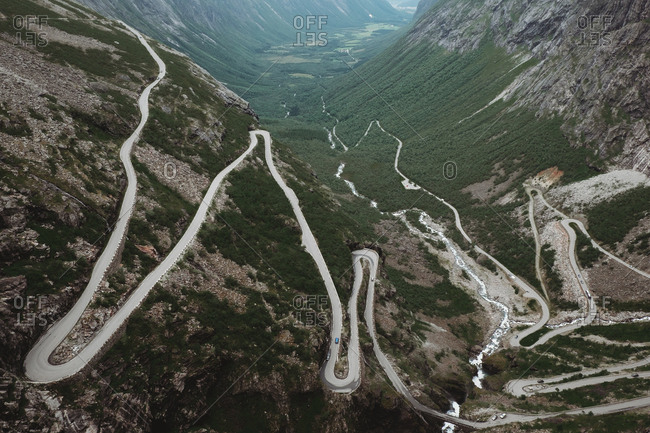 Aerial shot of long curvy pathway running on slope of rocky mountains in valley