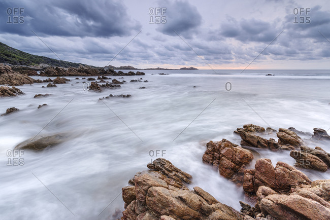 Seascape with long exposure water blur and fluffy clouds