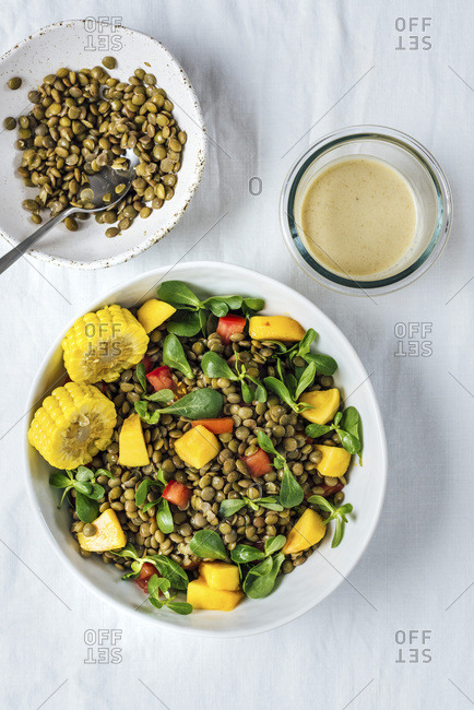 Lentil salad with herbs, tomatoes and peaches in a white bowl