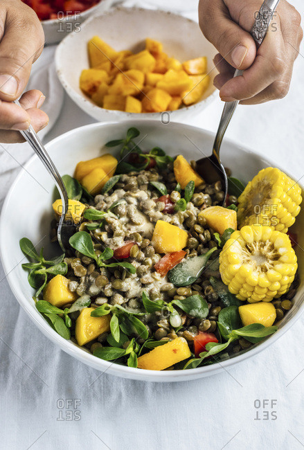 A woman stirs a bowl of lentil salad with herbs, corn and peaches
