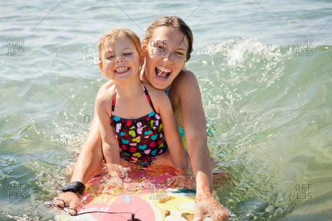 Mother and daughter boarding in ocean