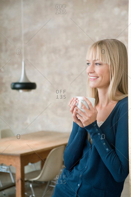 woman smiling and holding cup