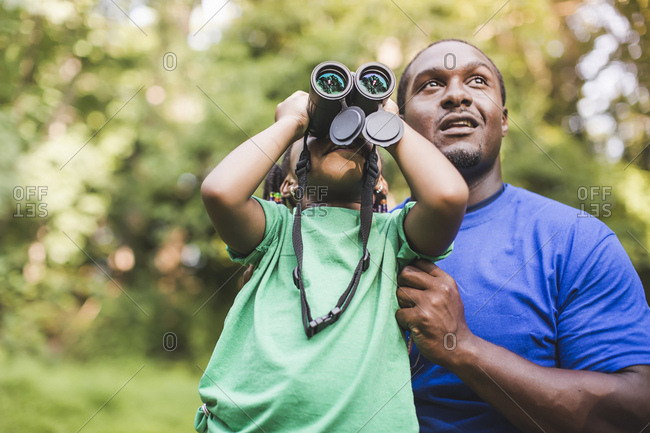 Young father and daughter bird watching in eco forest camp
