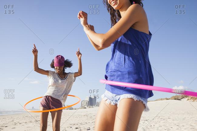 Women on beach using hula hoops