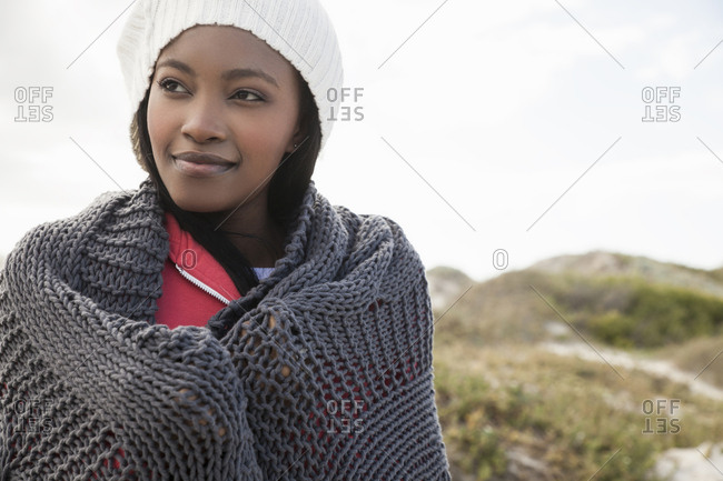 Young woman wrapped in knitted shawl on cold day