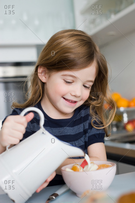 Girl putting milk into her bowl