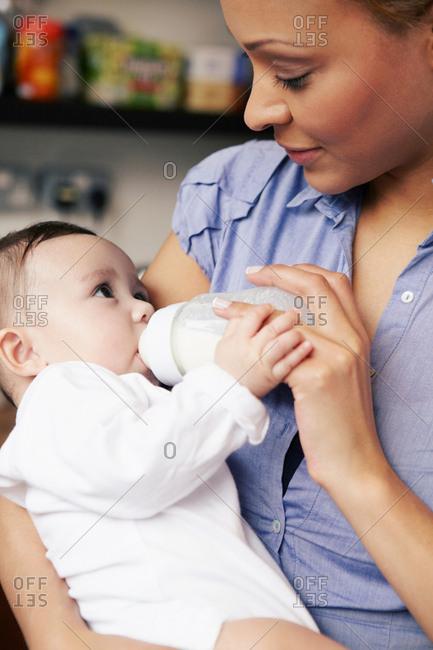 Mother feeding baby girl bottle of milk