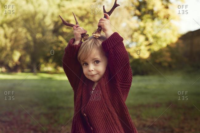 Toddler using sticks as antlers