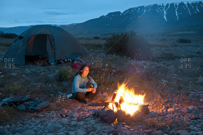 Woman sitting at campfire, Eyjafjordur, North Iceland