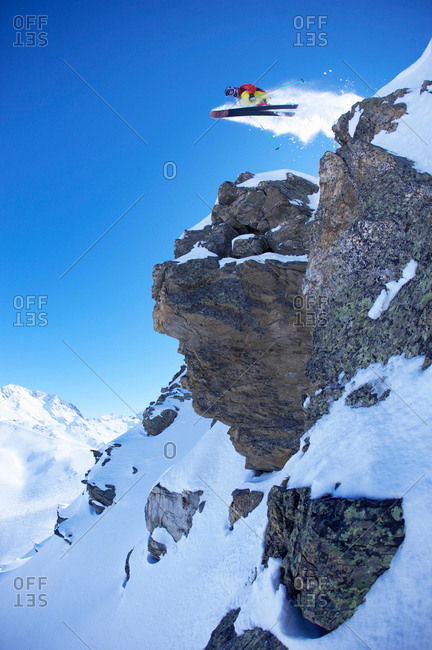 Extreme skier jumping from rock