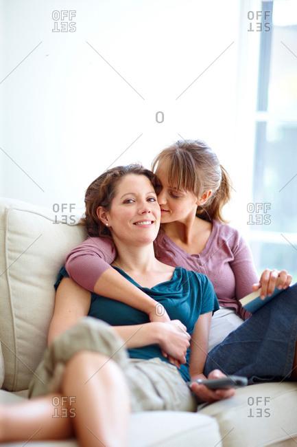 Two women watching TV cuddling