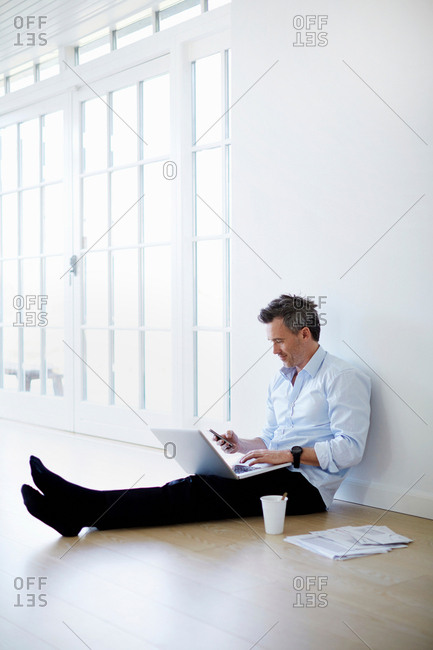 Man sitting on floor using laptop and phone