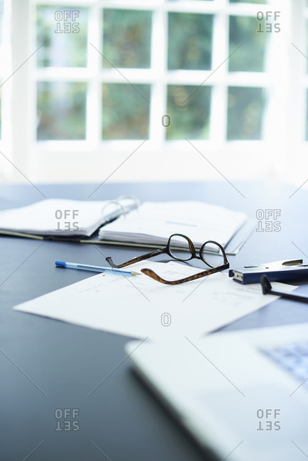 Laptop, eyeglasses and diary on dining room table