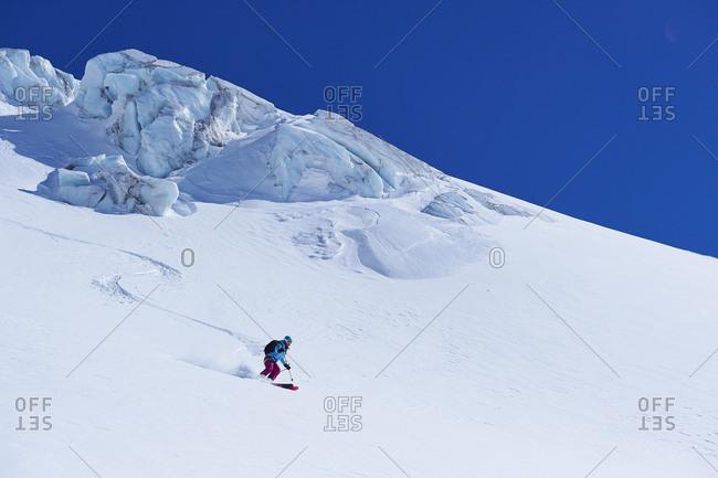 Female skier moving down Mont Blanc massif, Graian Alps, France