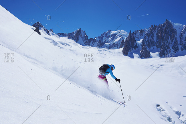 Mature female skier moving down Mont Blanc massif, Graian Alps, France