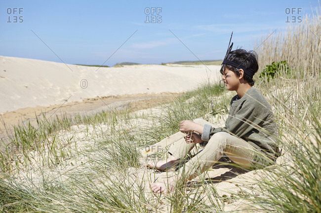 Young boy, wearing fancy dress, sitting on sand dunes