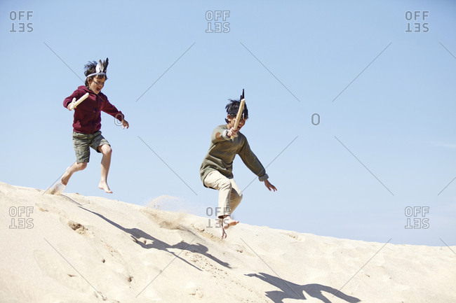 Two boys, wearing fancy dress, playing on sand