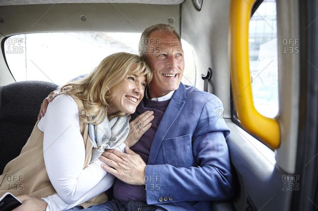 Mature romantic dating couple en route in black cab backseat