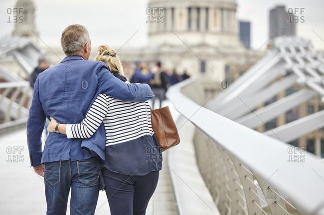 Rear view of mature dating couple  crossing Millennium Bridge, London, UK