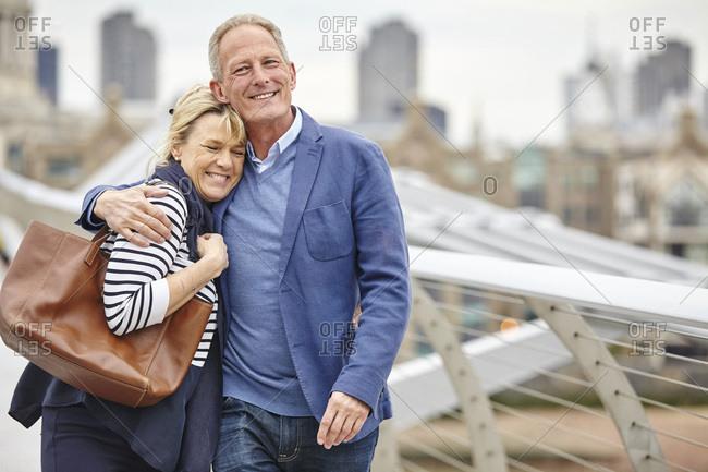 Mature dating couple strolling across Millennium Bridge, London, UK
