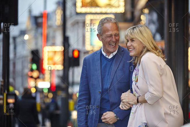 Mature dating couple giggling on city street at dusk, London, UK