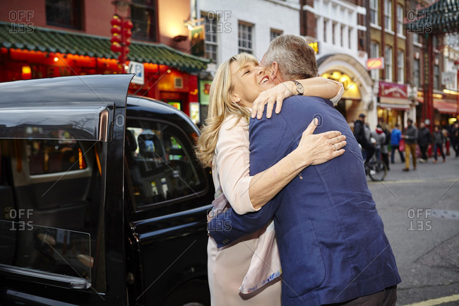 Mature dating couple hugging farewell in China Town, London, UK