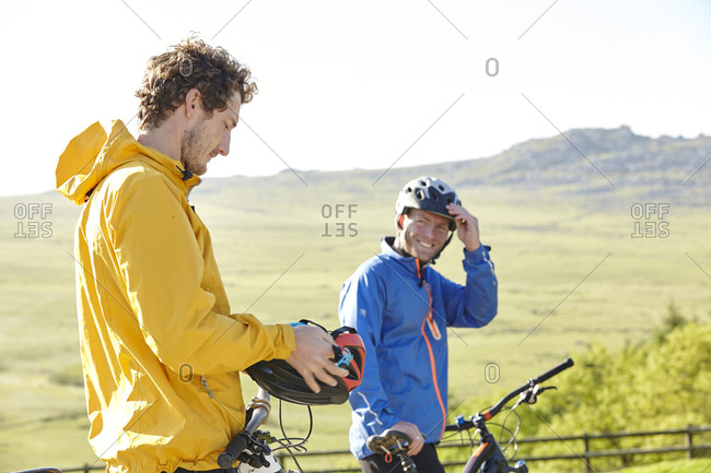 Cyclists putting on cycling helmets