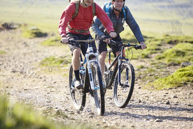 Cyclists cycling down dirt track
