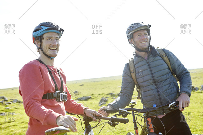 Cyclists on hillside holding bicycles looking away