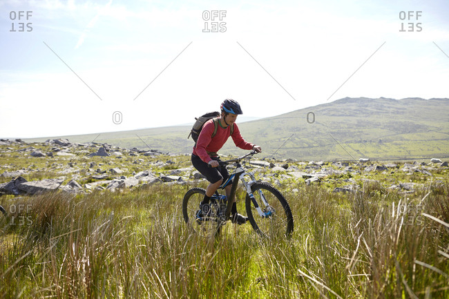 Cyclist cycling on hillside - Offset