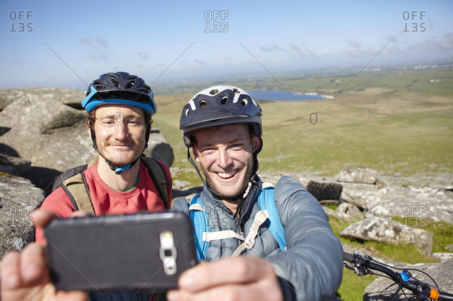 Cyclists with on rocky outcrop taking selfie