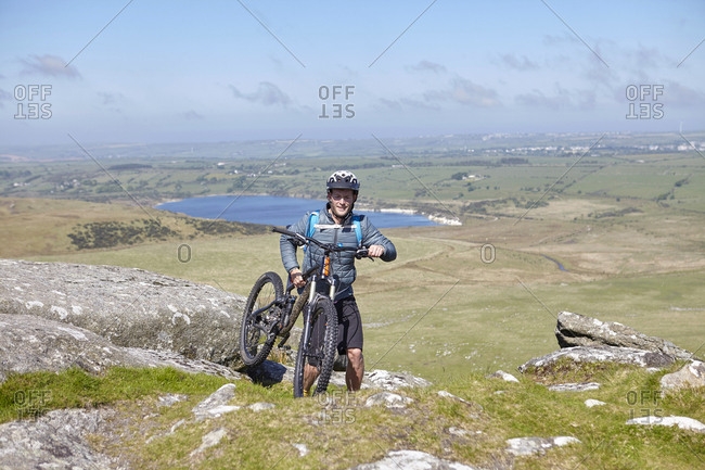 Cyclist carrying bicycle on rocky outcrop
