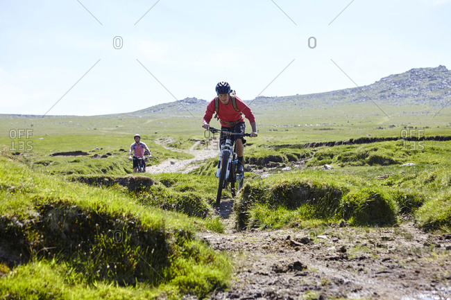 Cyclists cycling down hillside - Offset