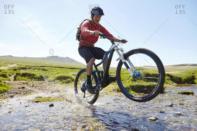 Cyclist doing wheelie through water