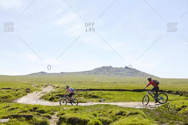Cyclists cycling on hillside path