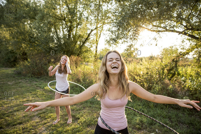 Two young girls in rural environment, fooling around, using hula hoops,