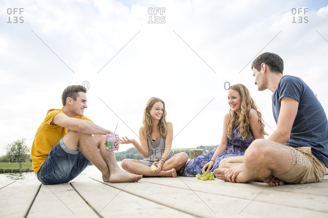 Group of young adults sitting on jetty, relaxing