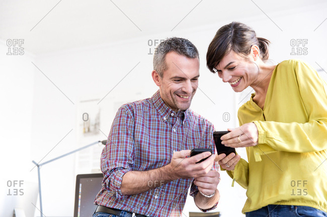 Low angle view of colleagues in office looking at smartphones smiling