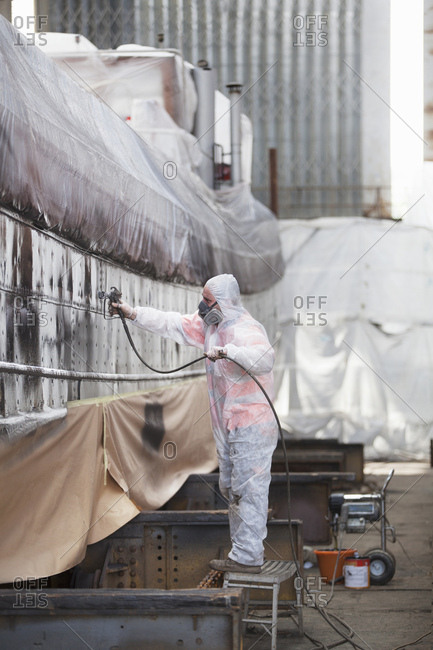 Worker spray-painting boat in shipyard